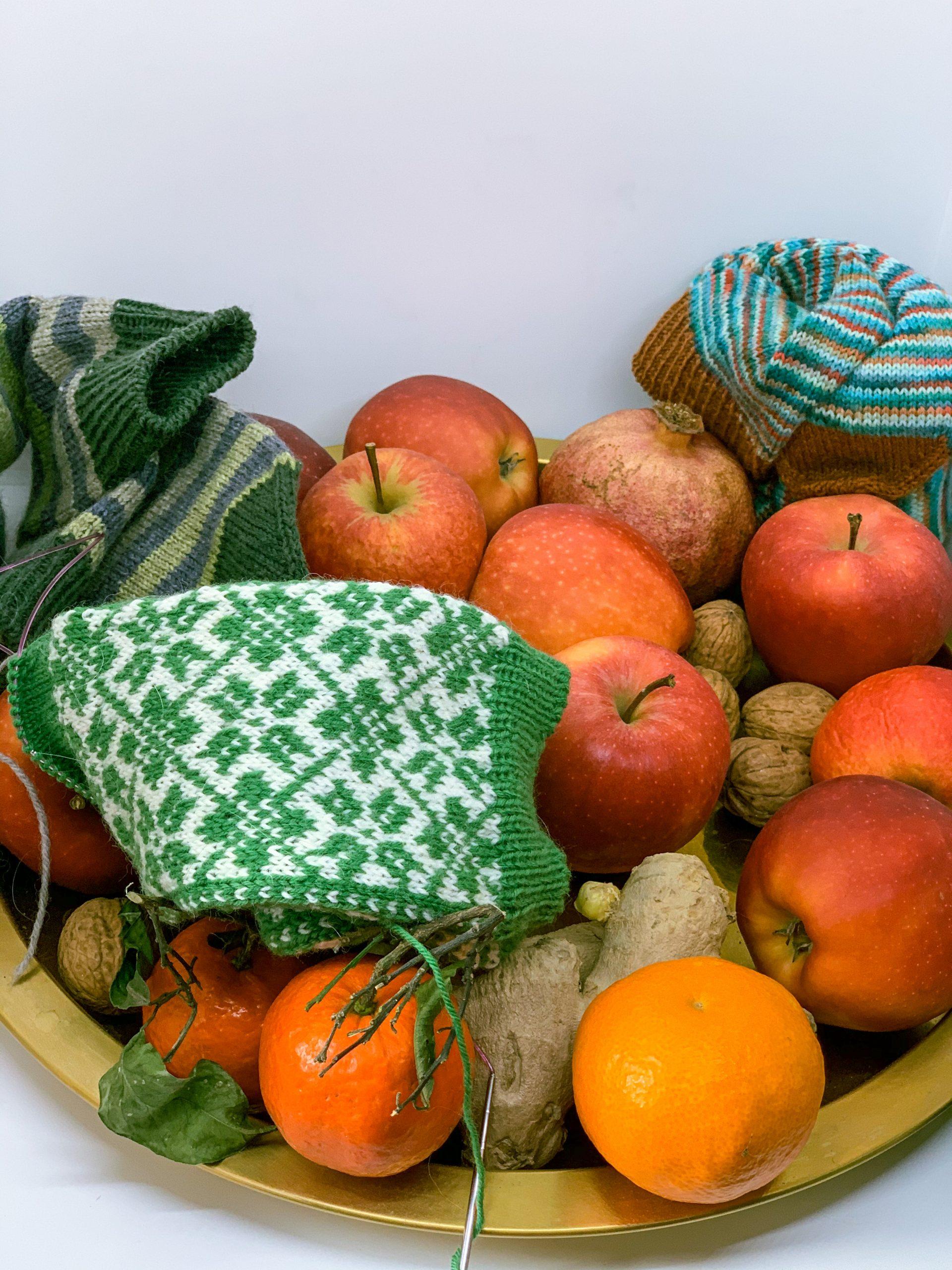 Nikolausteller mit grünen Wollsocken Mandarinen Nüssen Granatapfel Apfel und Ingwer